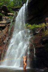 Beautiful slim fitness model posing sexy under waterfalls