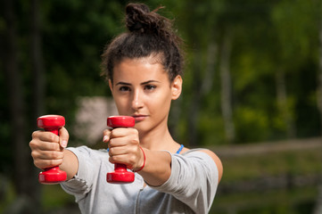 Woman exercising in the park with two red weights