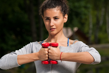 Attractive woman holding two weights together