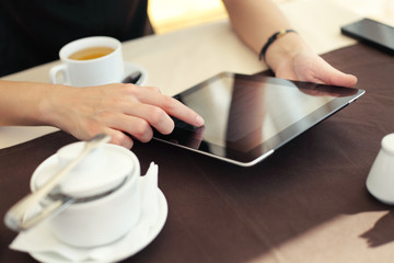 Image of woman hand pointing at tablet touchscreen in cafe