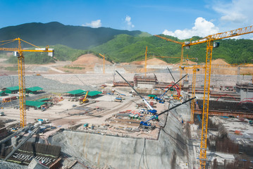 Huge construction site for dam with cranes in mountain area