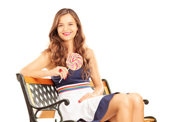 Beautiful brunette female sitting on a bench holding a lollipop
