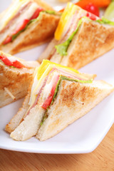 Sandwich with bacon and vegetables on white dish