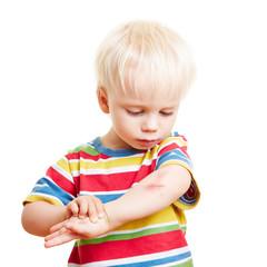 Kind schaut sich Verletzung am Arm an