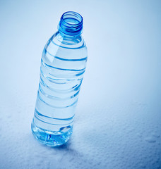plastic water bottle on wet blue background