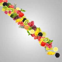 Waterfall of fruit and berries on gray background