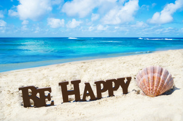 "Sign ""Be Happy"" and seashell on the sandy beach"