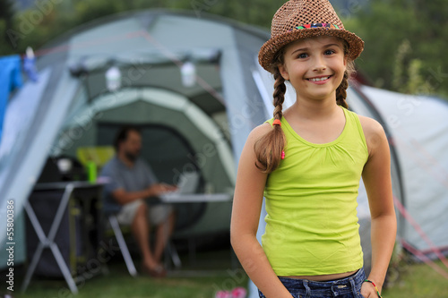 Camp in the tent - young girl with family on the camping