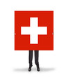 Smiling businessman holding a big card, flag of Switzerland