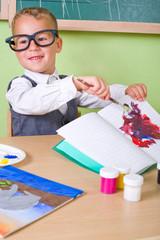 Kleiner Junge malt ins Schulheft
