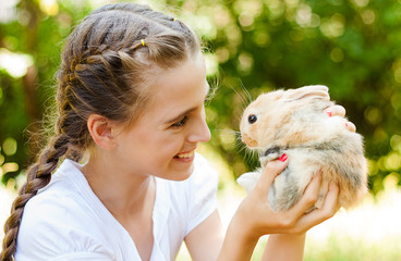 Cute little girl with a rabbit in the garden.