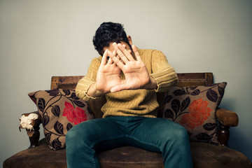 Young man on sofa covering his face