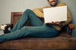 Smiling young man with laptop on old sofa