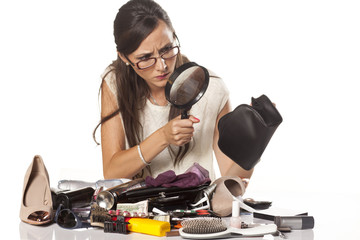 nervous girl searches inside of her bag by magnifying glass