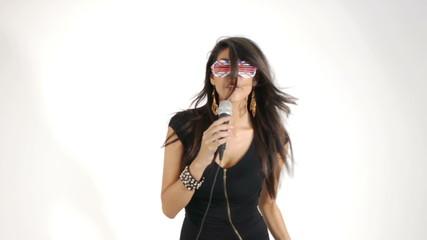Ragazza Sexy con occhiali che canta al microfono dinamico