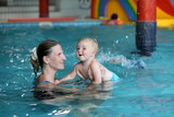 Young mother with cute baby training in swimming pool