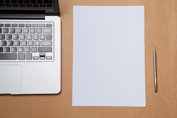 blank paper and laptop on table