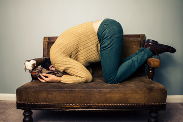 Young man burying his face in old sofa