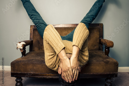 Tired young man is upside down on old sofa