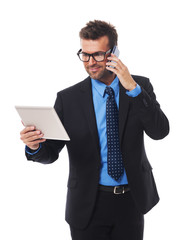 Busy businessman working on tablet and mobile phone