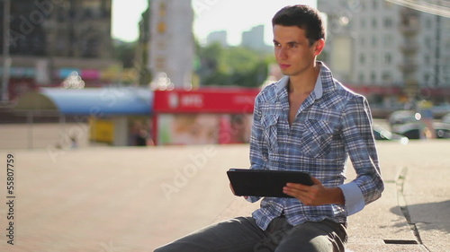 Young man sitting on square reading touch pad computer inspiring
