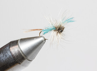 Hand tied fishing fly in clamp