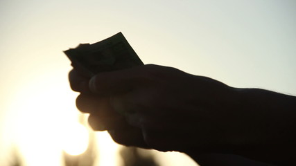 Silhouette of hands counting money folding stack of bank notes