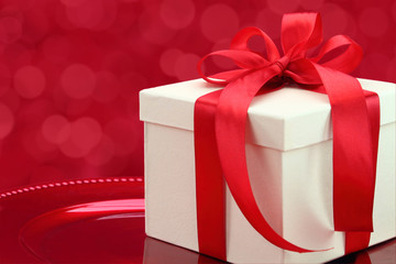 Gift box on a plate with elegant red lights background