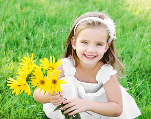 Cute little girl on the meadow with flower
