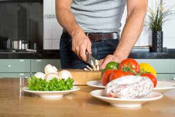 Midsection Of Man Cutting Vegetables At Kitchen Counter