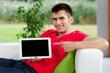 freundlicher mann zeigt auf ein tablet