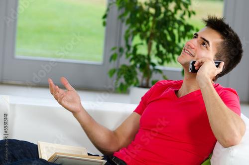 junger mann telefoniert auf der couch