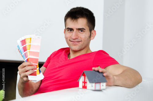junger mann mit haus und farbkarten