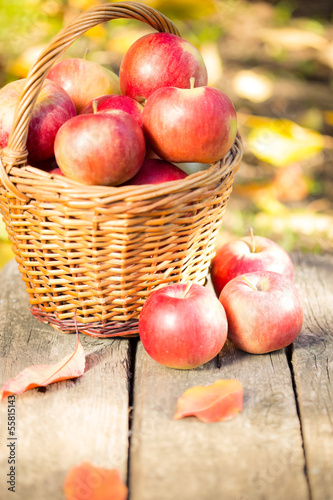 Basket with red apples on wooden table