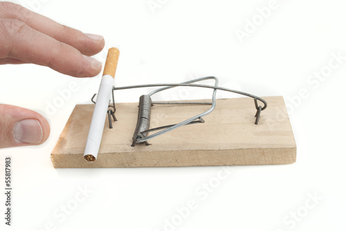 Hand reaching for a cigarette in mousetrap