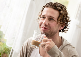 Man standing by a window drinking coffee