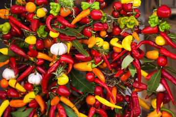 an Schnüren aufgehangene Chilis und Knoblauch