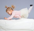 Happy little girl having fun on bed isolated on grey