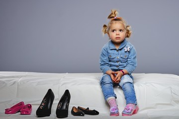 Disappointed little girl sitting on a bed