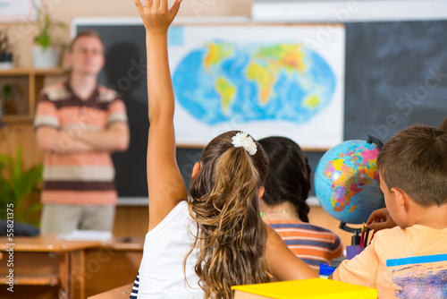 Schoolgirl rising her hand at geography lesson