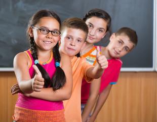 Four smiling schoolchildren standing in classroom