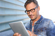 Man with blue jeans jacket using digital tablet