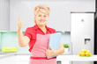 Female cooker in kitchen giving thumb up