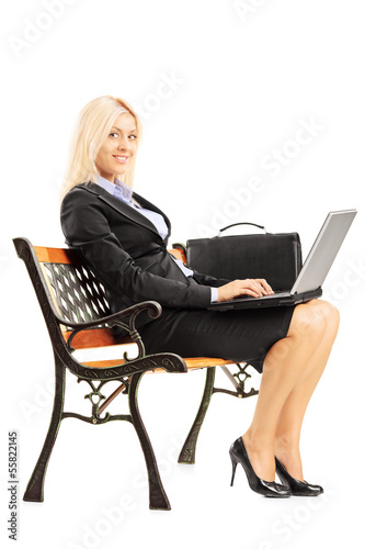 Smiling businesswoman sitting on a bench and working on a laptop
