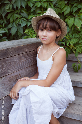 Cute girl in a hat sitting on the porch