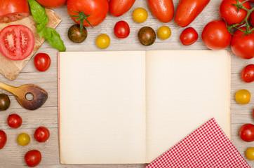 Verschiedene Tomaten, Basilikum, Kochlöffel und Buch mit Textfr
