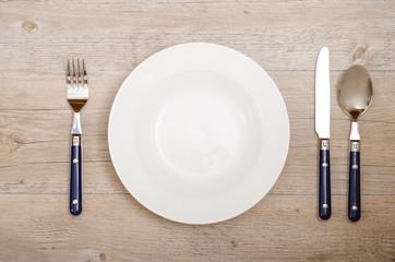 Gedeck aus Messer, Gabel und Löffel auf Esstisch