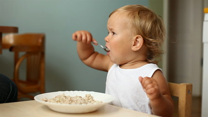 little girl eats porridge