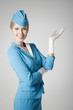 Charming Stewardess Dressed In Blue Uniform Pointing On Gray Bac