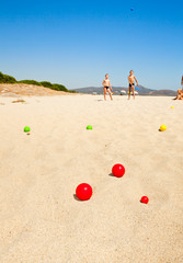 Children playing boules on a beach